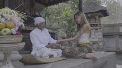 Balinese priest holding women's hand, palm reading in a small temple, ungraded Stock Footage