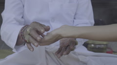 Balinese priest taking women's hand to do palm reading, ungraded Stock Footage