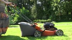 Gardener woman in spotty dress push lawn mower cutting meadow grass. 4K Stock Footage