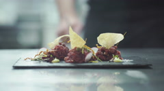 Chef is finishing gourmet meal (raw meat) at commercial kitchen in a restaurant - stock footage