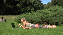Young woman lying on grass in park and using laptop. 4K Stock Footage