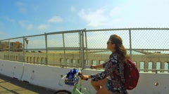 Cool shot of woman riding bike on bridge by ocean Stock Footage