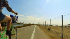 Woman riding a bicycle on path with other cyclists passing by. Stock Footage