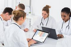 Group Of Multi-racial Doctors Using Laptop At Desk - stock photo