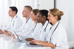 Group Of Multi-racial Doctors Using Laptop In Meeting - stock photo