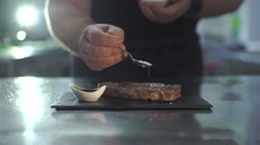 Chef is sprinkled with salt beef steak Stock Footage