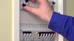 Hand checking and turning on circuit breakers in electrical fuse box at his Stock Footage
