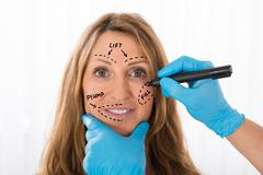 Close-up Of Happy Mature Woman With Perforation Lines Marked On Face Stock Photos