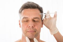 Close-up Of Mature Man Get Injection On His Face - stock photo
