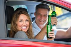 Close-up Of Happy Mature Couple Sitting Inside The Car Enjoying Beer Kuvituskuvat