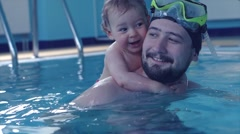 father teaching son to swim in the pool - stock footage