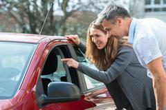 Happy Couple Looking At New Red Car In Auto Salon Stock Photos