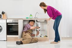 Male Plumber Repairing Pipe Under Sink While Woman Standing In Kitchen Stock Photos