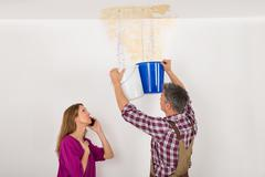 Worker Collecting Water In Bucket From Ceiling While Woman Talking On Mobile  - stock photo