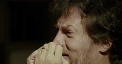 Desperate man crying at home at night closeup Stock Footage