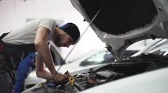 Auto mechanic repair engine in a car repair shop Stock Footage