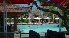 Tourists enjoying the pool at a luxury resort hotel in Sanur, Bali, Indonesia - stock footage