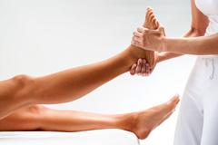 Osteopath massaging female foot. Stock Photos