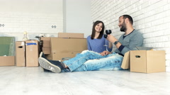Young, happy couple talking and drinking wine on floor at their new home Stock Footage