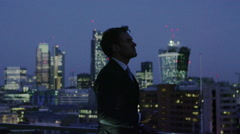 4K Successful businessman with cell phone looks out over London skyline at night - stock footage