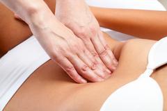 Therapist Hands pressing on female abdomen. Stock Photos