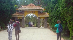 Tourists pause for photos beneath the entry arch of a popular public park - stock footage