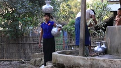 Burmese girl with big jugs with water. Mrauk U , Burma, Myanmar Stock Footage