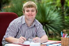 Boy with down syndrome at desk outdoors. Stock Photos