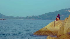 Local man fishing from the rocks in Phuket, Thailand, with sound - stock footage