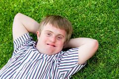 Handicapped boy relaxing on green grass. Stock Photos