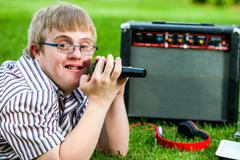 Handicapped boy singing with microphone and amplifier. Stock Photos