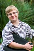 Young student with down syndrome holding files outdoors. Stock Photos