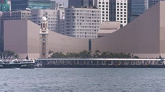 Ferry transiting in front of the Tsim Sha Tsui clock tower. UltraHD footage Stock Footage
