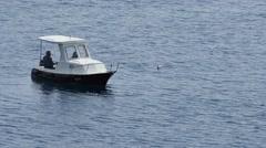 Fisherman fishing on calm seas Stock Footage