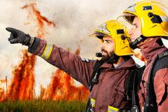 Firemen indicating fire to companion. Stock Photos