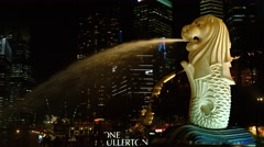 Merlion fountain dominates dramatically lit night time cityscape of Singapore Stock Footage