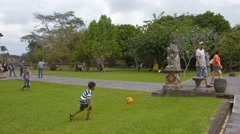 Childen playing football in Taman Ayun Temple. Bali, Indonesia Stock Footage