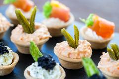 Multiple mini pastry tartlets with seafood filling. Stock Photos
