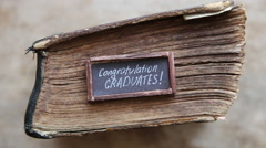 Congratulations graduates text and vintage book on table Stock Footage