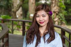 Filipina woman on a bridge in a garden - stock photo