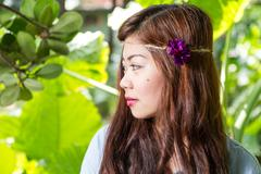 Side profile of Filipina woman in a garden - stock photo