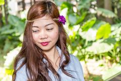 Filipina woman in a garden looking away from camera - stock photo