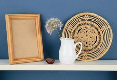 photoframe and vase with a flower on white  shelf on blue wallpaper - stock photo