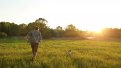 Man running with his dog Jack Russell on a meadow at sunset Stock Footage