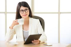Asian attractive businesswomen using Digital Tablet and drinking coffee - stock photo