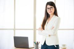 Asian attractive businesswomen arms crossed standing in office - stock photo