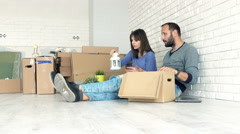 Young couple packing things to boxes sitting on floor Stock Footage
