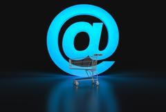 Concept of e-commerce. Big @ sign and empty shopping cart on black background Piirros