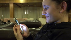 Smartphone girl using app on phone smiling in hotel lobby Arkistovideo