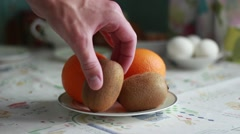 Man putting citrus fruit on a plate Stock Footage